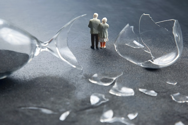 Miniature people. elderly people walk near the broken hourglass. loss of life time. crisis of hope and problems of old age