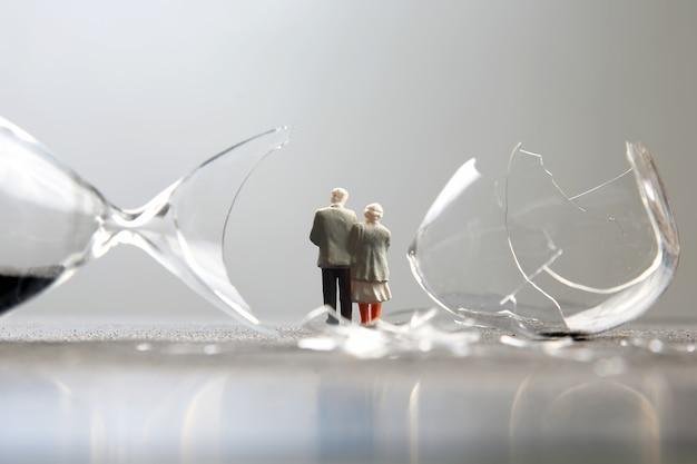ミニチュアの人々。高齢者は壊れた砂時計の近くを歩きます。寿命の損失。希望の危機と老後の問題