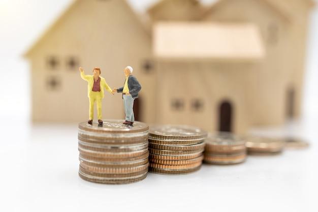Миниатюрные люди: пожилой человек, стоящий на стеке монет с домом, концепция планирования выхода на пенсию.