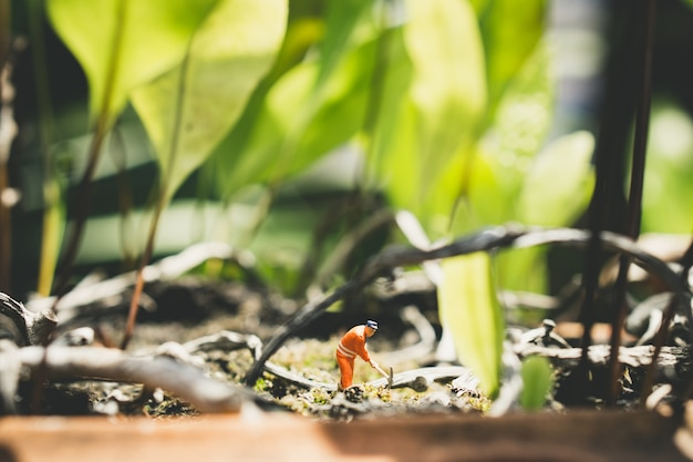 Miniature people engineer on green nature used for concept work hard