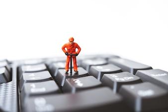 Miniature people, engineer standing on computer keyboard