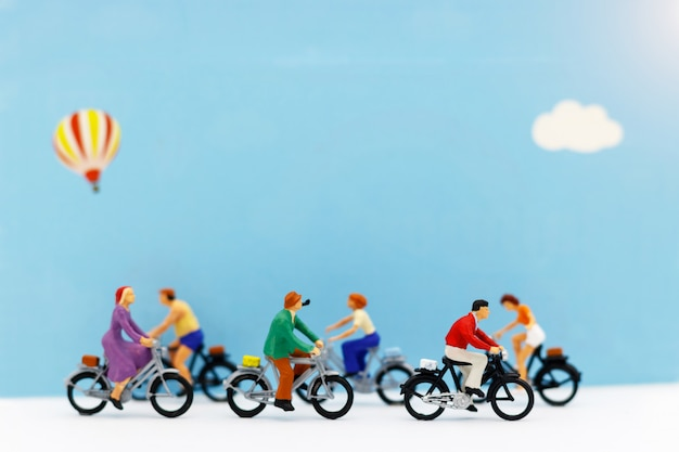Miniature people enjoy riding a bicycle on blue background.