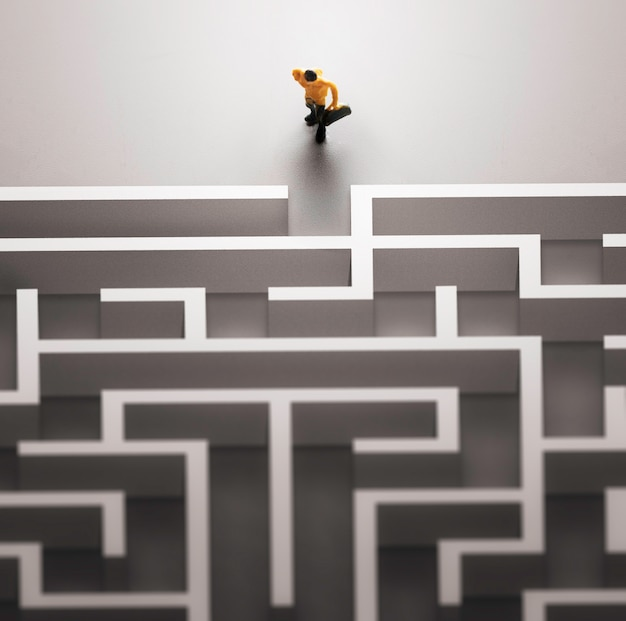 Miniature people entering a maze. problems in life  concept.