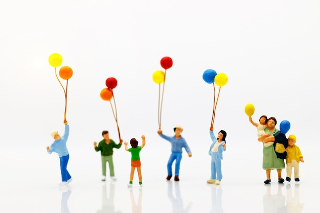 Miniature people, family and children enjoy with colorful balloons.