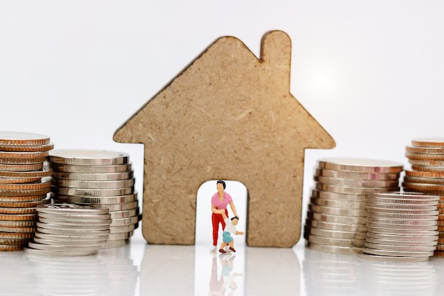 Miniature people, family and children enjoy with home and coins stack.