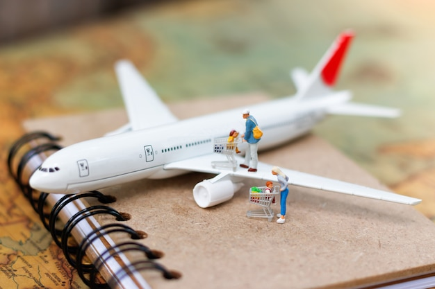 Miniature people family with shopping cart on airplane.