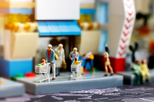 Miniature people family with shopping cart in supermarket.