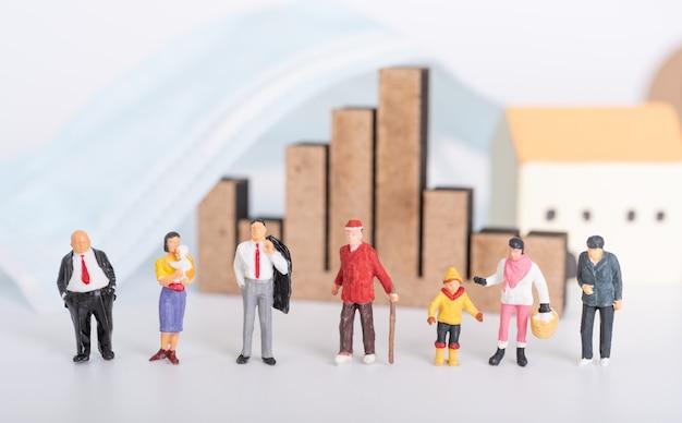 Семья миниатюрных людей с хирургической маской, бизнес-графиком и значком дома на белом