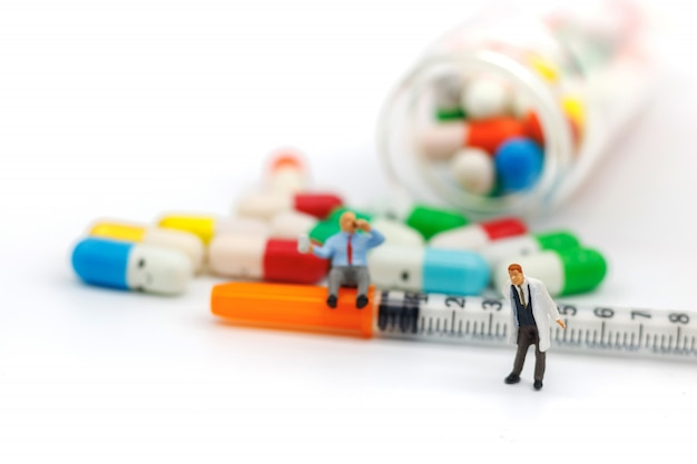 Миниатюрные люди: толстые пациенты сидят на шприце с наркотиками и часами. концепция здравоохранения.