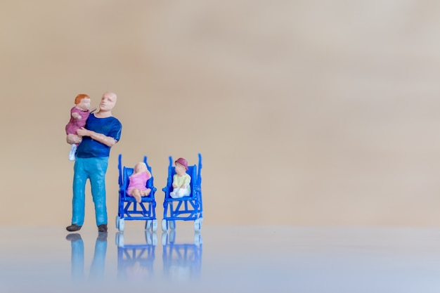 Miniature people father holding their cute baby daughter in the arms Premium Photo