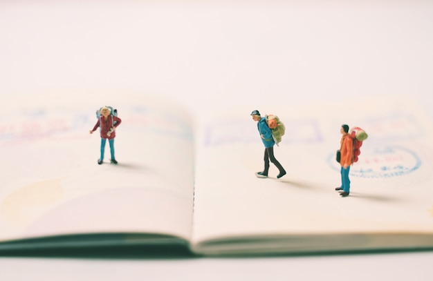 Miniature people figures with backpack walking and standing on passport page with immigration stamps, travel and vacation concept
