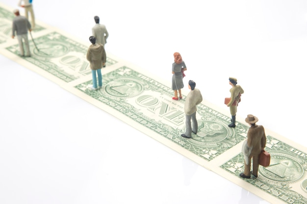 Miniature people. figurines of people walk the road from dollar money to their success in life. financial independence concept