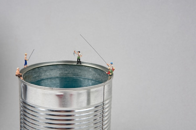 Miniature people fishing on cans