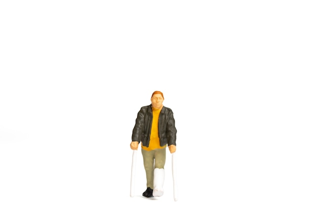 Miniature people , full length view of a man with broken leg is using crutch on white background.