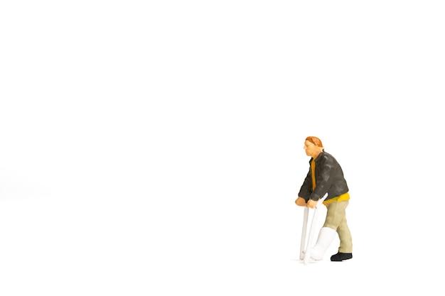 미니어처 사람들, 부러진 다리를 가진 남자의 전체 길이 보기가 흰색 배경에 목발을 사용하고 있습니다.