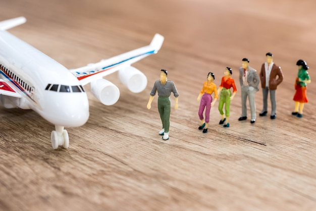 Miniature people go to the airplane