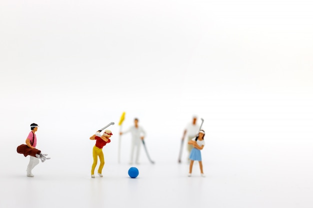 Miniature people: golfers hit golf balls forward. target and growth in business concept.