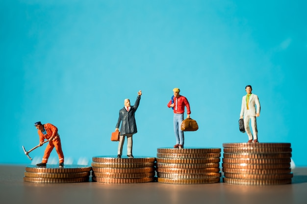 Miniature people, group of businessman standing on stack coins