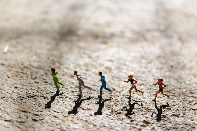 Miniature people : group of people are running  on concrete floor