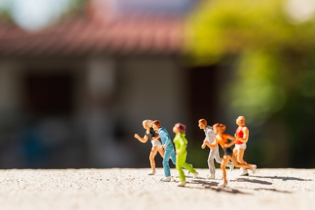 Miniature people : group of people are running  on concrete road