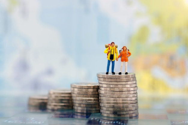 Miniature people: happy couple backpacker standing on coins stack.
