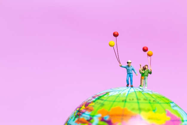 Miniature people : happy family holding balloon on the globe with pink background