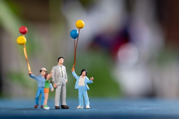 미니어처 사람들 : 공원에서 풍선을 들고 행복한 가족 프리미엄 사진