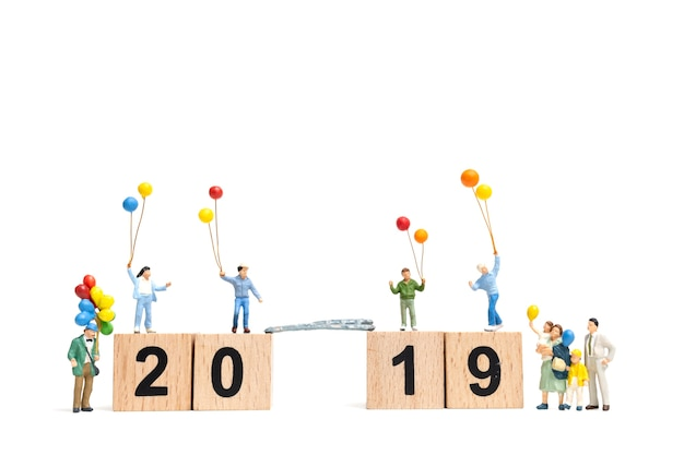 Miniature people : happy family holding balloon on number 2019 and copy space for text