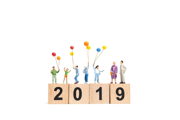 Miniature people : happy family holding balloon on number 2019