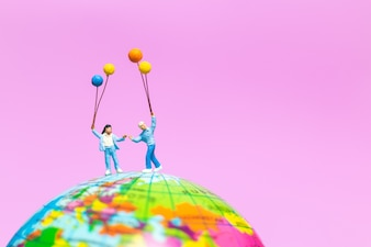 Miniature people: Happy family holding balloon on The globe with pink background