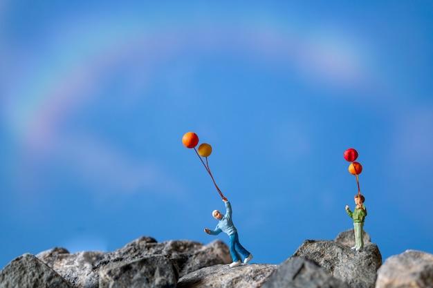 미니어처 사람들, 푸른 하늘과 바위에 풍선을 들고 행복한 가족