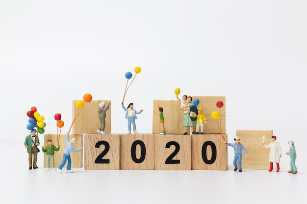 Miniature people: happy family holding balloon on wooden block number 2020