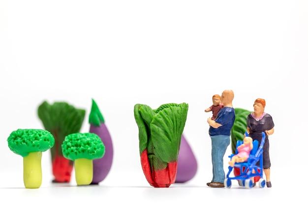 미니어처 사람들은 야채 농장에서 쉬고 있는 행복한 가족입니다. 세계 채식주의의 날 개념