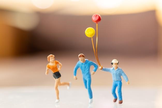 미니어처 사람들이 행복한 가족 실행 및 풍선, 어린 시절 및 가족 개념을 가지고 노는.