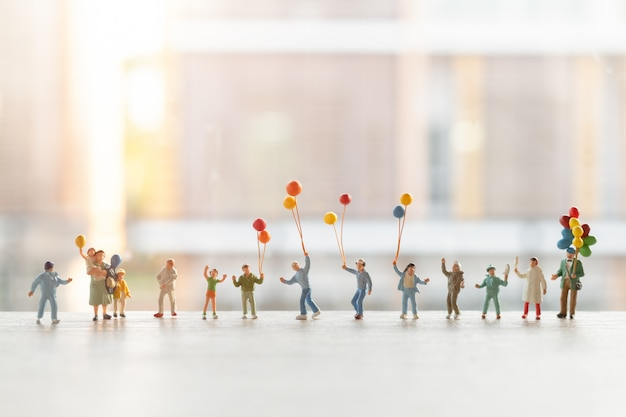 Miniature people : happy family walking with balloons