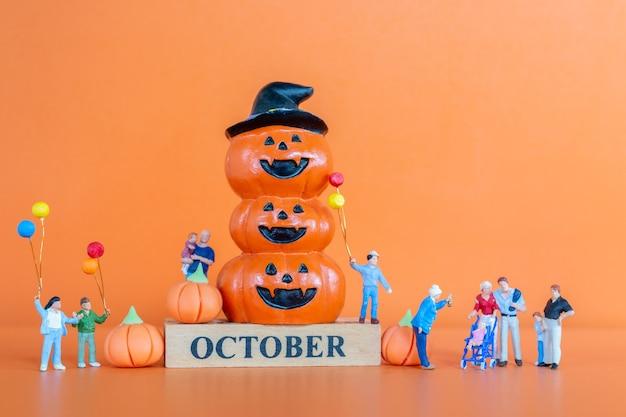 주황색 배경에 호박이 있는 미니어처 행복한 가족, hello 10월 개념