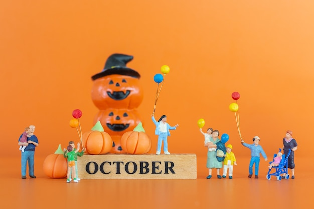 Miniature people happy family  with pumpkin on orange background, hello october concept