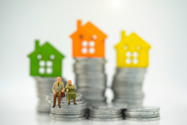 Miniature people: happy old people standing with home, retirement planning.