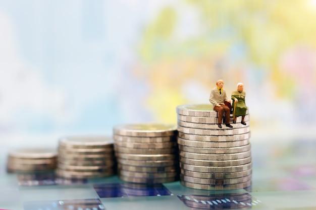 Миниатюрные люди: счастливые старшие пары сидя на стоге монеток, концепция выхода на пенсию.