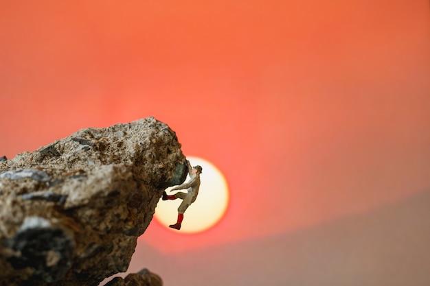 ミニチュアの人々:岩の上に登るハイカー。スポーツとレジャーのコンセプトです。