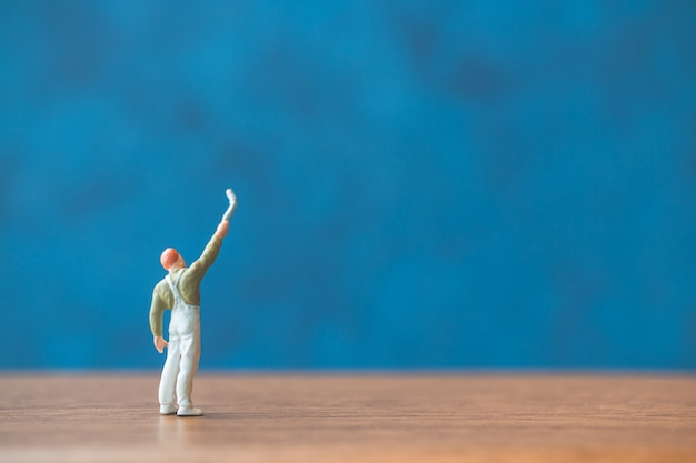 Miniature people holding brush in front of a blue wall background