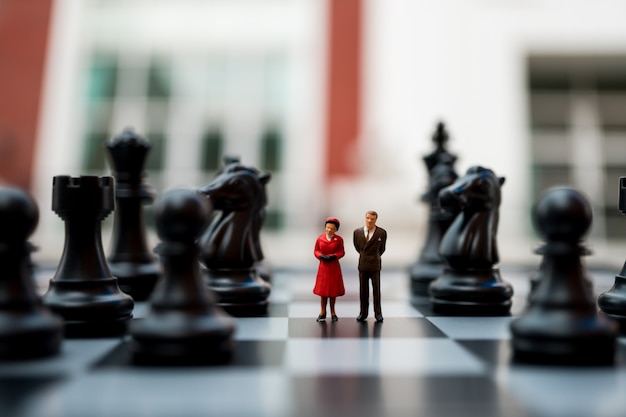 Miniature people, husband and wife standing on chess board background using as business concept