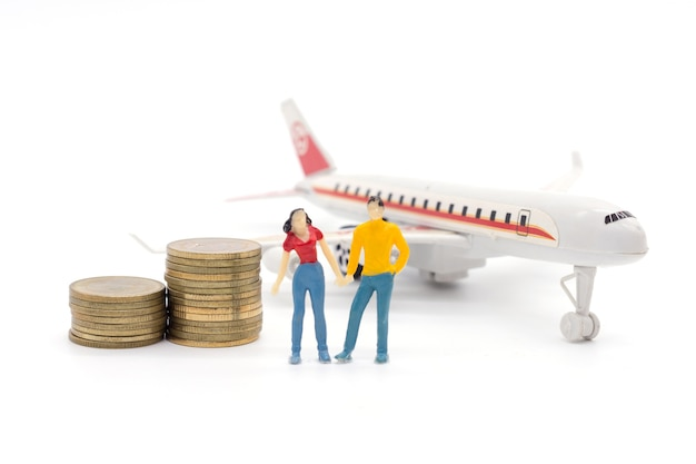 Miniature people,husband and wife standing with airplane and stack coins. saving and loan concept.
