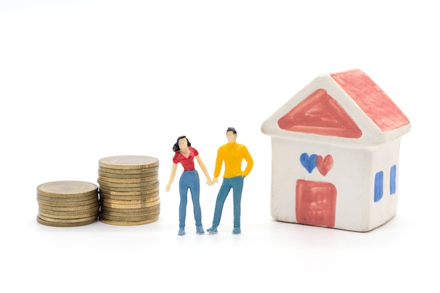 Miniature people,husband and wife standing with house and stack coins. saving and loan concept.