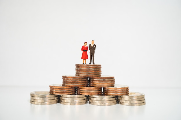 Miniature people, husband and wife standing with stack coins