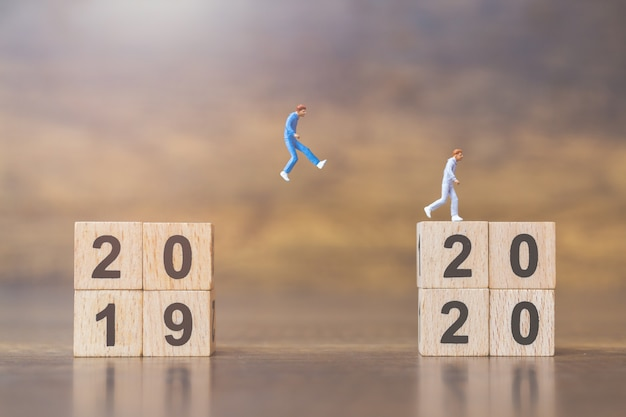 Miniature people jump from number 2019 to 2020