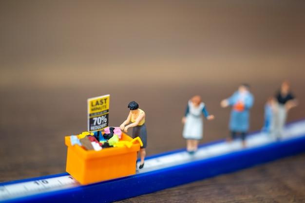 ミニチュアの人々は、ショッピングモールや公共エリアで距離を保ちます。社会的距離の概念。