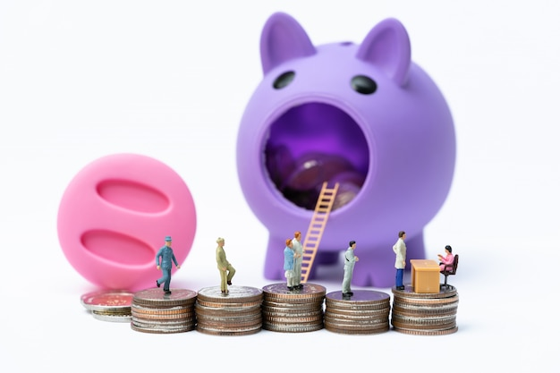 Miniature people in line at the bank counter on the stack of coins in front of piggy bank.
