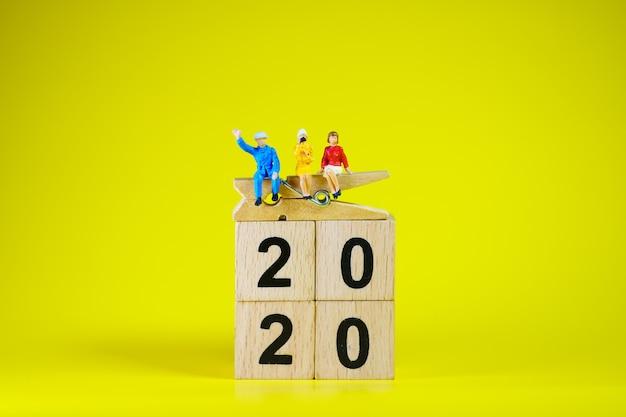 Миниатюрные люди, мужчина и женщина, сидящие на деревянном блоке 2020, используя как бизнес-концепцию