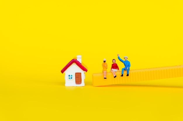 ミニチュアの人々、ビジネス会議や社会的概念として使用して黄色の背景にミニ家と一緒に座っている男性と女性